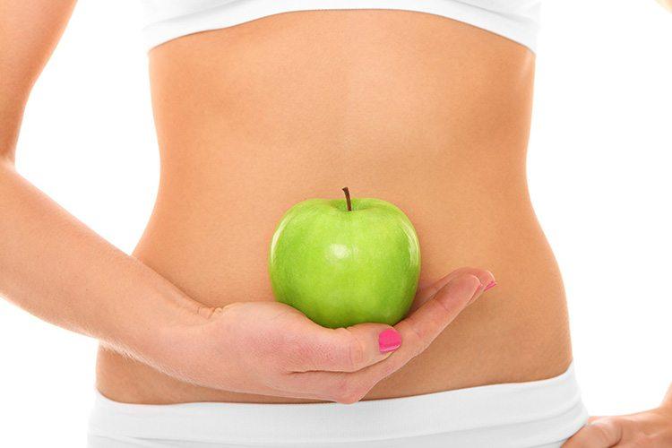 mujer-con-manzana-en-mano-enfrente-del-abdomen