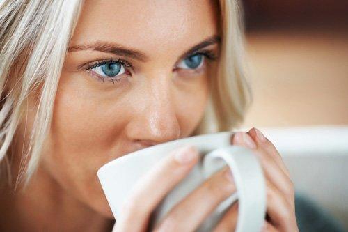 mujer-ojos-azules-bebiendo-cafe
