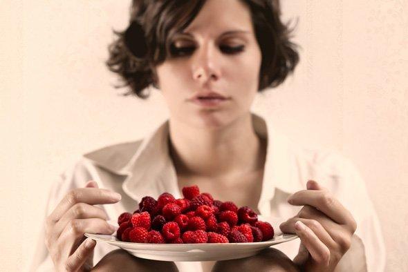 mujer-sosteniendo-plato-con-frambuesas