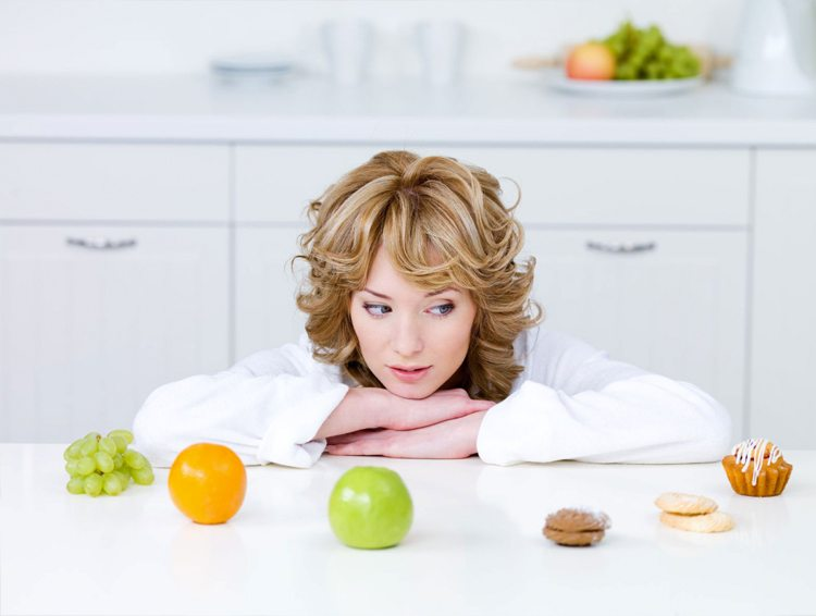 mujer-con-uvas-naranja-manzana-dulces